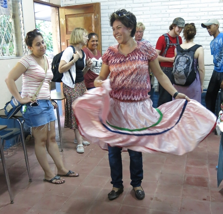 Mirna, W/NP Managua office manager dancing in a skirt crafted by an Ometepe learning center.